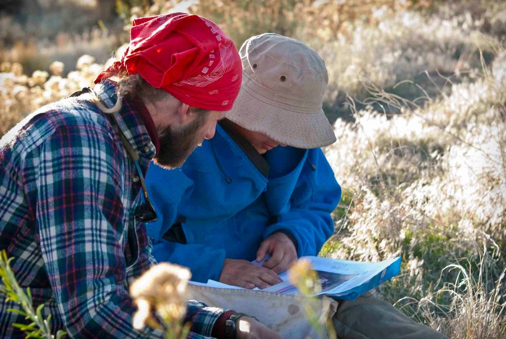 A guide sits with a student at Open Sky Wilderness Therapy.