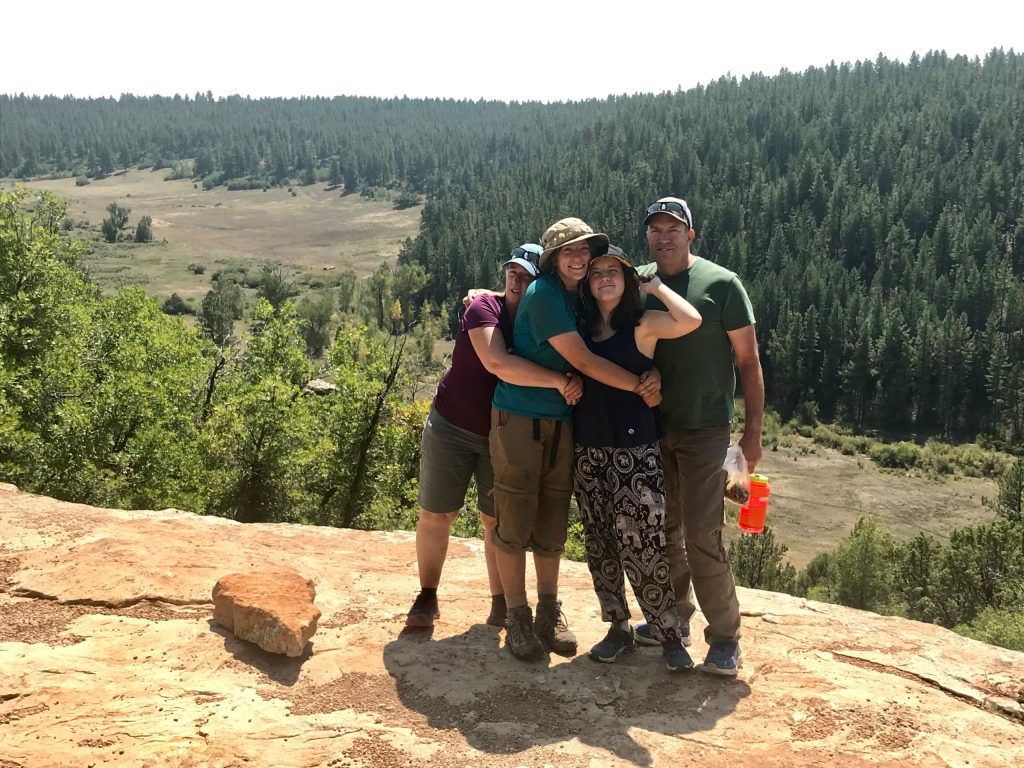 A family hugs one another on a rocky outcropping at Open Sky Wilderness Therapy.