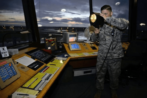 Air Force air traffic controller uses a light gun to transmit messages to pilots
