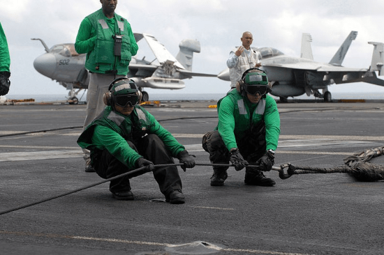 green shirts on an aircraft carrier