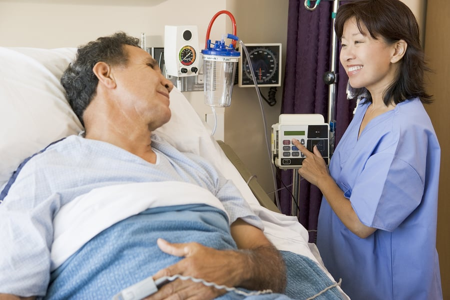 Male norco patient on hospital bed with woman nurse standing next to him
