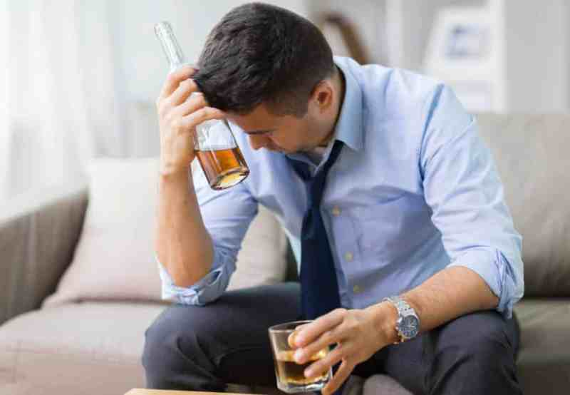 alcoholism, alcohol addiction treatment and people concept - male alcoholic with bottle and glass drinking whiskey at home