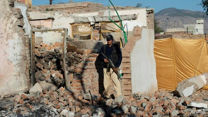 A policeman stands guard outside the Hindu temple destroyed by a Muslim mob in Pakistan