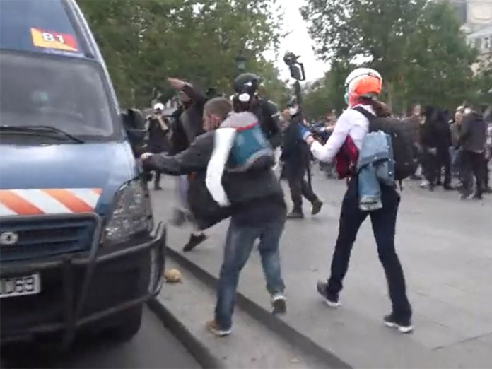 Protester breaking Police vehicle