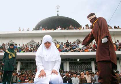 A shariah law officer canes a woman in front of a mosque in Banda Aceh, Indonesia, Friday, Jan. 27, 2006. This woman is blamed for staying together with her boy friend in a house. (AP Photo/Binsar Bakkara)