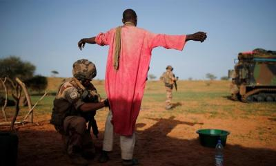 A French soldier searches a man during an area control operation in the Gourma region during Operation Barkhane in Ndaki