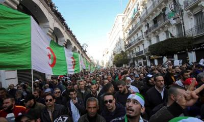 Demonstrators carry a national flag during an anti government rally in Algiers on January 3 2020