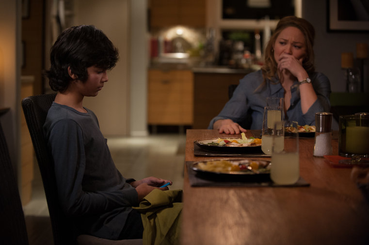 Parenthood, young boy using phone, worried mom, annoyed mom, dinner table