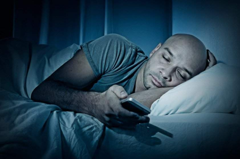 young cell phone addict man sleeping at night in bed while using smartphone