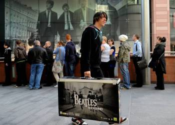 "Beatles fans queue outside the HMV music store in Liverpool, north west England during the rush to purchase the new Beatles Rock Band interactive computer game and digitally remastered albums, on September 9, 2009. A new wave of Beatlemania swept around the world Wednesday as the Fab Four's digitally remastered albums and a new computer game were released. Fans queued up from Tokyo to London to get their hands on the rejuvenated and cleaned-up versions of all the legendary British quartet's entire back catalogue, and the ""The Beatles: Rock Band"" game. AFP PHOTO/PAUL ELLIS / AFP / PAUL ELLIS"