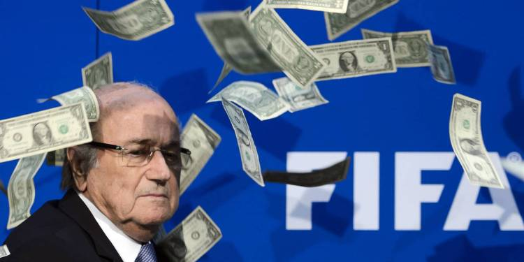 (FILES) This file photo taken on July 20, 2015 shows FIFA president Sepp Blatter looking on with fake dollars note flying around him thrown by a protester during a press conference at the football's world body headquarter's on July 20, 2015 in Zurich.   Sepp Blatter earned 3.6 million Swiss francs ($3.7 million) in 2015, FIFA said on March 17, 2016 as it revealed the fallen world football leader's salary for the first time.  / AFP / FABRICE COFFRINI