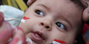 A baby has Egypt's national flag drawn on her face on a street in Cairo November 14, 2009. Egypt hosts Algeria for their 2010 World Cup qualifying playoff soccer match on November 14.   REUTERS/Tarek Mostafa (EGYPT SPORT SOCCER)