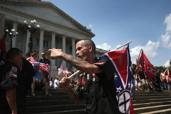 COLUMBIA, SC - JULY 18: Counter protesters and Ku Klux Klan members argue at a Klan demonstration at the state house building on July 18, 2015 in Columbia, South Carolina. The KKK protested the removal of the Confederate flag from the state house grounds and hurled racial slurs at minorities as law enforcement tried to prevent violence between the opposing groups. John Moore/Getty Images/AFP