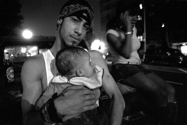 21 year old gang member Pedro holds his newborn.