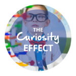 "The words ""The Curiosity Effect"" overlay an image of a young person looking at a colorful structure who is wearing dark glasses, a red bow tie, a blue shirt, and a lab coat. Click to learn more about The Curiosity Effect."