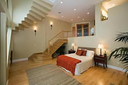 Oak Stairs Leading Down To A Unique Split Level Master Bedroom