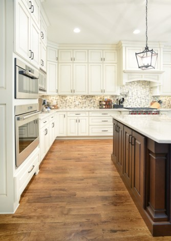 Sole Design Cabinetry. Perimeter: Braden door style. Painted Ivory w/ Chocolate Glaze. Island: Braden door style. Rustic Alder wood, stained Brown Sugar w/ black glaze.