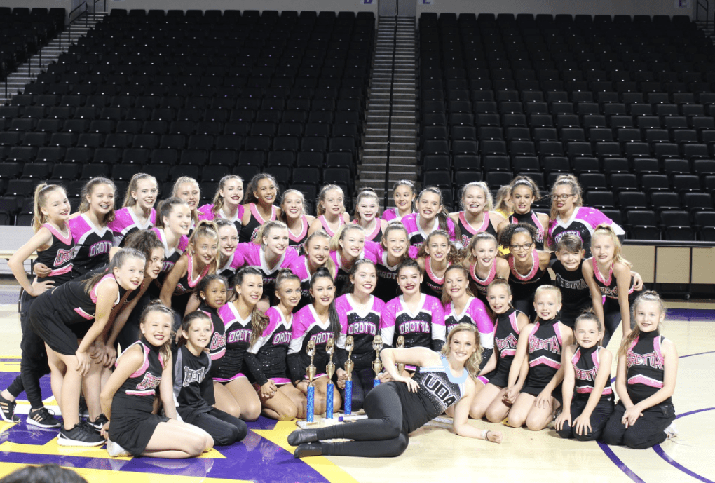 group of dancers with championship trophy