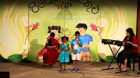 Scene from Pipen Kakulu 2015. The kids singing a song about two siblings arguing whether mom or dad loves them more - big brother is in the background and finally settles the argument at the end of the song.
