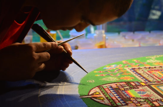 "Shanu, youngest of the Gaden Shartse Tibetan monks on the tour, works on a Manjushri Sand Mandala. The thin funnel in his hand is called a ""chakpur"" and is especially made for this task. A thin metal stick is used to ""ratchet"" or vibrate the funnel so it sends a controlled, thin stream of sand in fine lines to make the details and background colors. Rather than being laid ""flat,"" the sand is fact mounded into ridges and troughs, creating a brocade-like effect. Photo by: Tripp Mikich"
