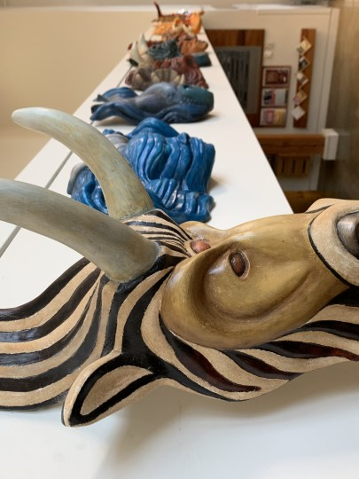 """""""Capricorn, the Goat,"""" from Kike Mayer's """"Zodiac"""" mask series, greets visitors from above the lobby the Chehalem Cultural Center in Newberg. Photo by: David Bates"""