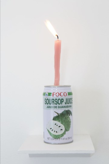 Can of FOCO brand soursop juice with a lit pink tallow candle emerging from the top, on a gallery shelf.