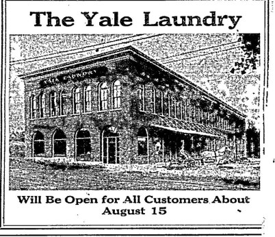 "Archival black and white newspaper photograph of Yale Union building, a flat-roofed two-story brick building with large arched windows on the ground floor and narrower arched windows on the second story. Headline reads ""Yale Laundry will Be Open for All Customers About August 15."""