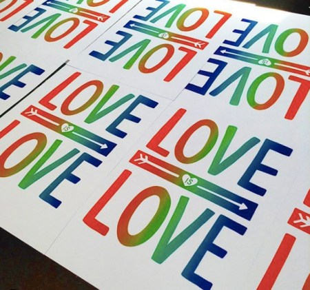 """Many screen printed posters laid out on a table, each one reads """"love is love"""" in rainbow ink."""