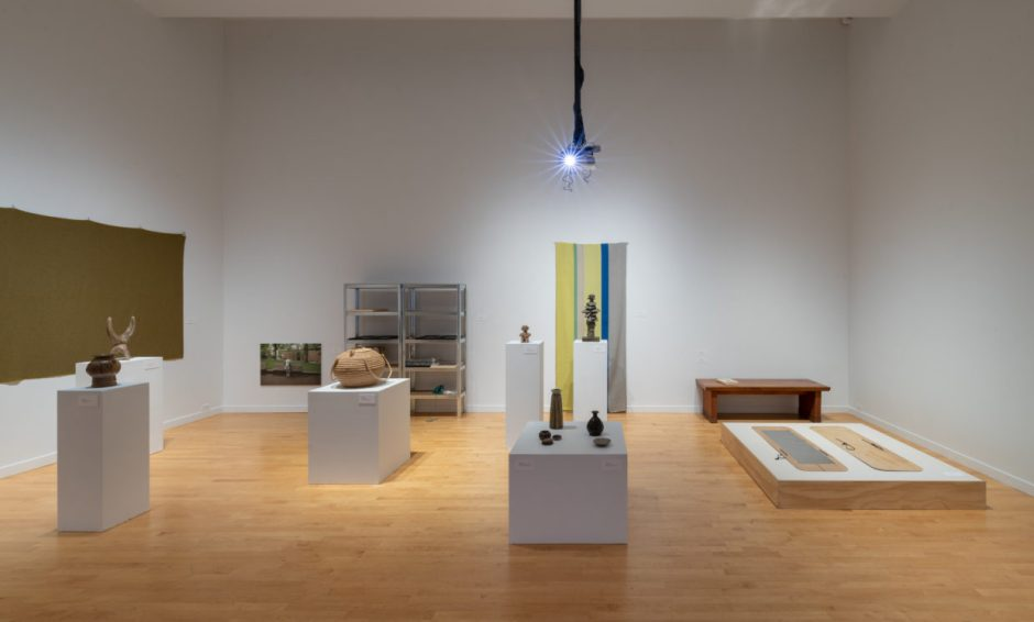 A white-walled gallery with several pedestals of varying heights displaying ceramics and a basket, woven wall hangings, flat artworks on a low dais, utility shelves, and a ceiling-mounted projector