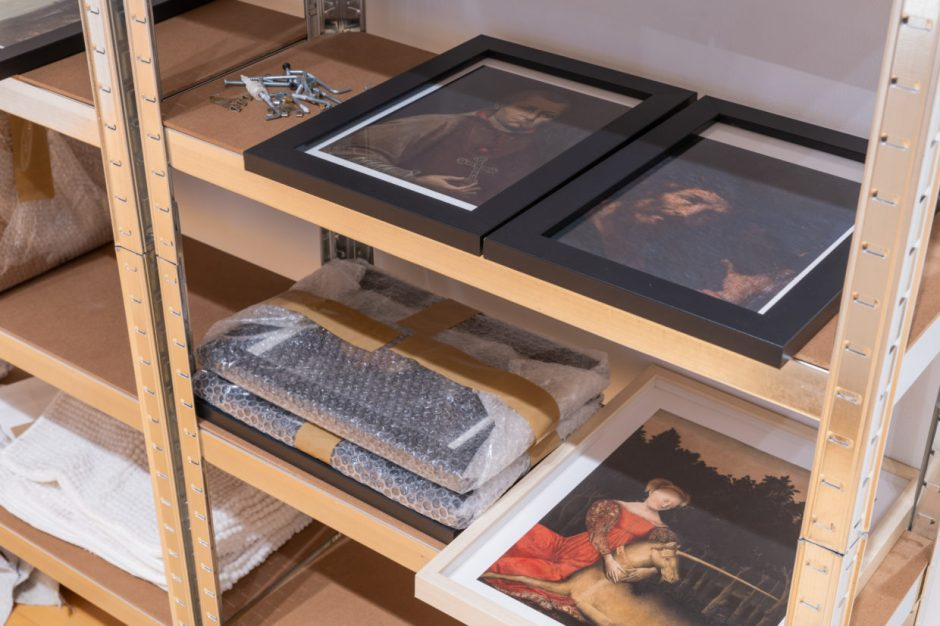 A wood and metal utility shelf with framed pictures of antique European paintings lying flat on  shelves, some stacked and packaged in bubble wrap. A small pile of screws and other hanging fixtures is also on the shelf.