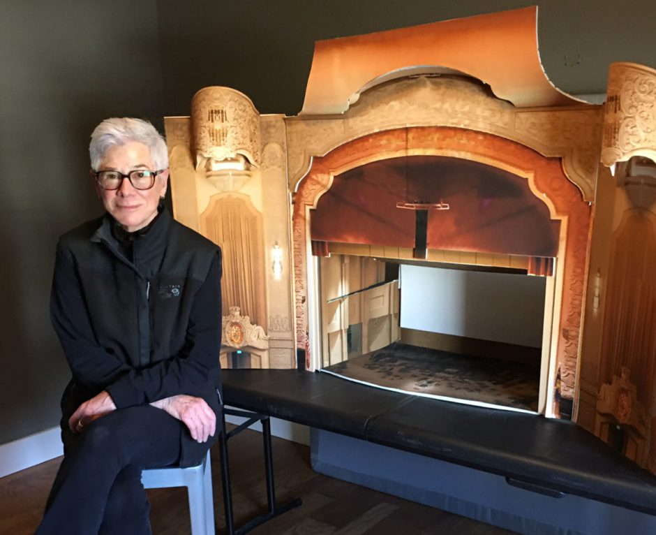 Artist Rose Bond seated in front of a scale model of the Arlene Schnitzer Concert Hall, Bond wears black athletic gear, black-rimmed glasses, and close cropped light gray hair, the model concert hall sits on a folding table in the gray room