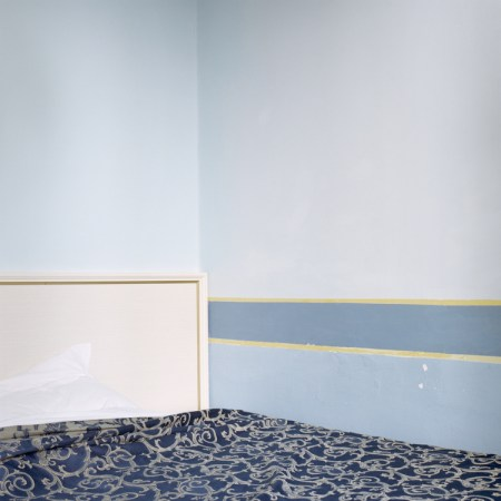 Photogrpah of a bed pushed into the corner of a room, the walls are painted in complementary blocks of light blue and yellow pinstripes, and the bed sports a dark blue and yellow coverlet with an arabesque pattern, which contrasts with the stark white headboard