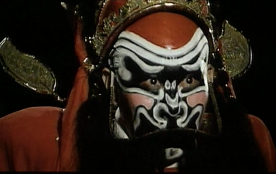 Film still of an actor with an intense expression wearing elaborate Chinese opera makeup in shades of red, white, and black