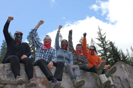 Five people sitting on a cliff edge raising their right hands in fists towards a blue sky, all wear outdoorsy outfits and bandanas wrapped around their faces to obscure their noses and mouths.