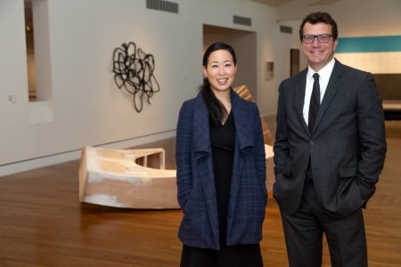 A woman with long black hair in a low ponytail, dressed in a navy blue plaid coat with a draped collar and simple black dress, poses in an art gallery featuring contemporary sculptures, to the right of a man wearing a gray business suit and black tie, with square-framed glasses