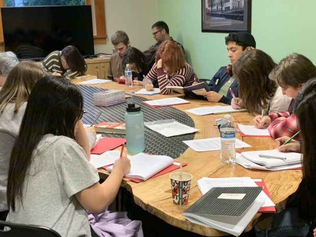 """Fire Writer students focus on a writing prompt during a session on exploring magical realism with Keith Rosen, author of two novels, """"Smoke City"""" and """"The Mercy of the Tide."""" Photo by: David Bates"""