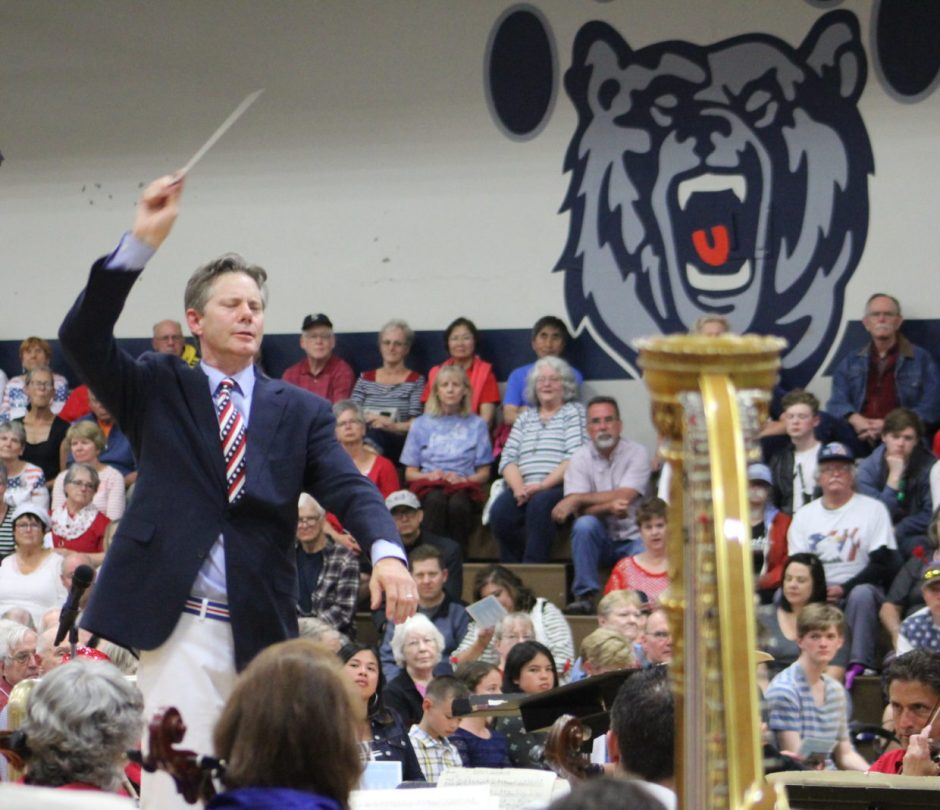 Under the growling gaze of the Newport Middle School mascot, Conductor Adam Flatt leads the Newport Symphony Orchesstra during the 2017 Fourth of July concert. The performance will be broadcast Saturday in lieu of a live event. Photo courtesy: Newport Symphony Orchestra