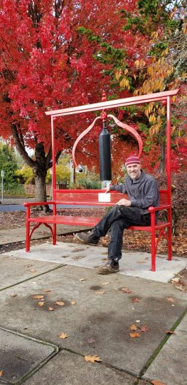"""Sculptor Jud Turner with """"The Wishing Bench"""" in Forest Grove."""