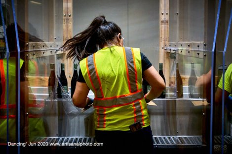 """Chitty calls the bottling crew the true heroes of the winery. In """"Dancing"""" (June 2020), he has captured a woman working on a section of th line that has been divided by perspex screens in response to the pandemic. """"We see her reflection and get a glimpse of her neighbors on the line. She is dancing her way through the task, drumming along to Latin beats. There is joy here, which the pandemic-driven precautions cannot suppress."""""""