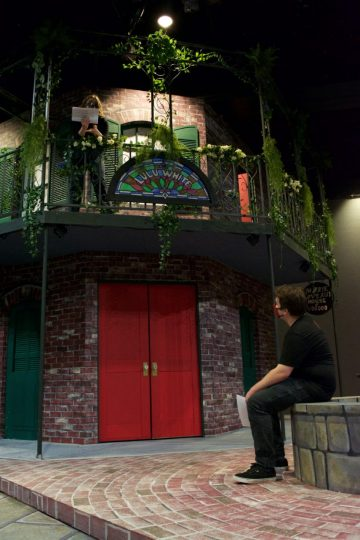 """Linfield students Abbie Northrop (on balcony) and Weston Lawrence rehearse a scene from """"A Night in New Orleans."""" The scenic design is by Robert Vaughn. Photo by: Clementine Dorsey"""