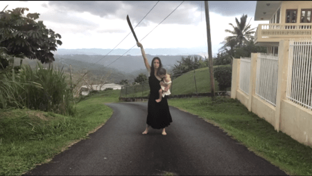 Still from the project Bodies Apart, Moving Together. Woman standing in a road holding a baby on her hip and a sword aloft.