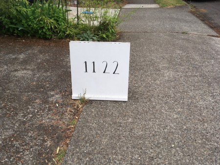 white sandwich board with the letters 1122 in hand-painted letters
