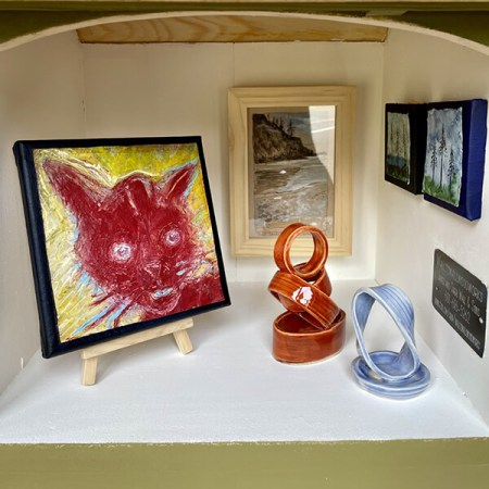 """The """"Sage Green"""" gallery at Manzanita's Hoffman Center for the Arts holds a red cat painting by Susan Walsh; Short Sand Beach watercolor by Dorota Haber-Lehigh; watercolors by Tammy Litwinchuk; and ceramic sculptures by Mary Roberts (22 by 17 by 15 inches, spruce with southern yellow pine roof; Plexiglas window)."""