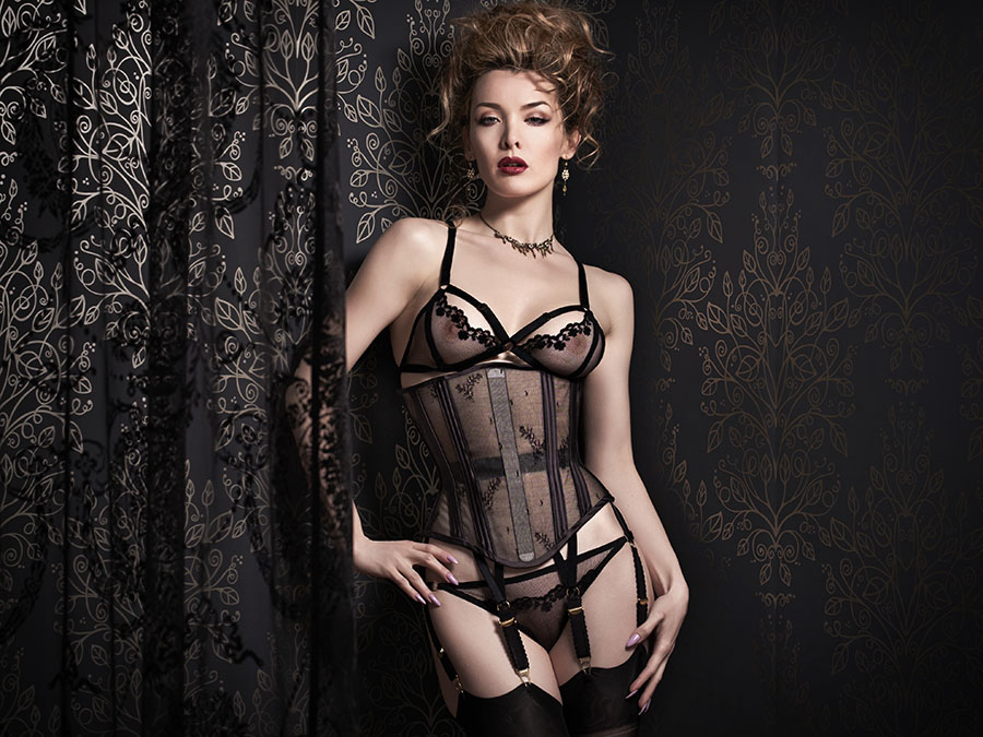 Model wears sheer black underbust corset and matching lingerie.