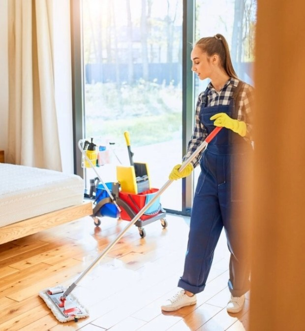 Woman Cleaning a Bedroom