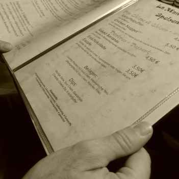 Speisekarte mit Kennzeichnung der Zusatzstoffe in der Hand eines Gastes