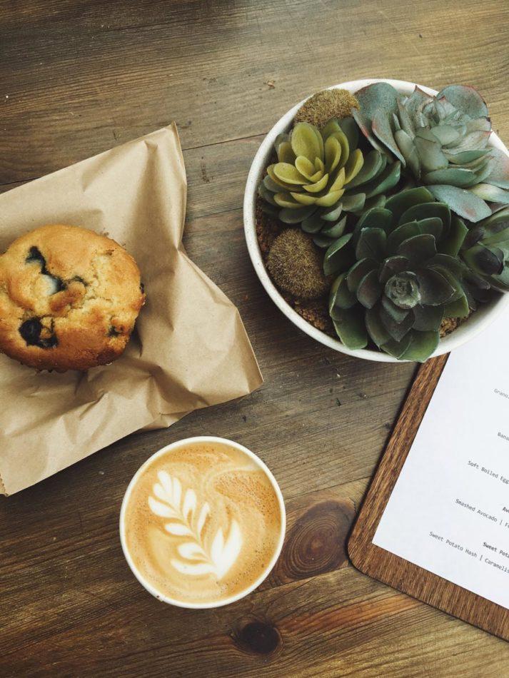 Ein Kaffee, ein Muffin und eine Speisekarte auf dem Tisch