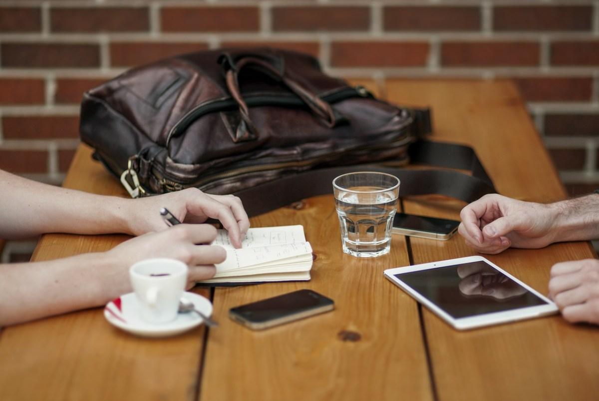 Tisch mit Handys und Notizbuch