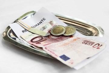 Geldschein und Münzen in einer Schale für Trinkgeld
