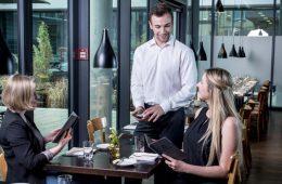 Funkbonieren: ein Kellner funktboniert am Tisch mit zwei Gästen.